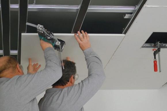 Mitarbeiter der CMS Fassadengestaltung GmbH befestigen eine Platte zum Abhängen der Decke