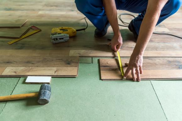 Ein Mitarbeiter der CMS Fassadengestaltung GmbH misst eine Laminat platte aus