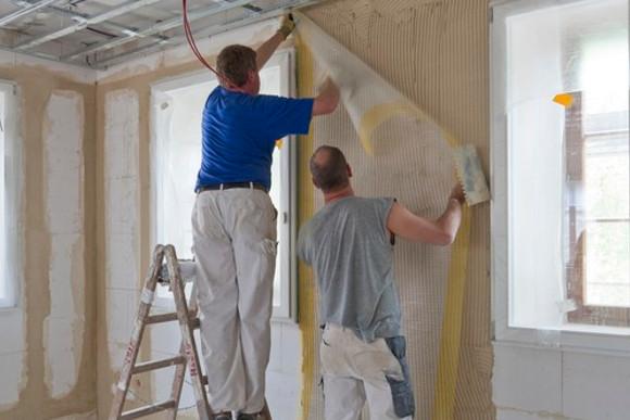 Schutzfolie anbringen an einer Verputzen Wand von CMS Fassadengestaltungs Mitarbeitern