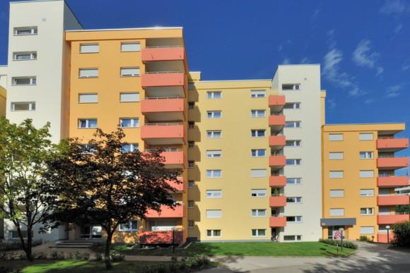Fassadenanstrich von Wohnblöcken in Gelb, Orange und Weiß