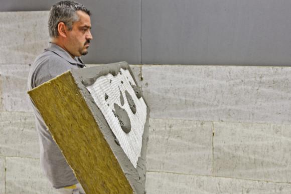WDVS-Platte wird von einem Mitarbeiter zur Wand getragen