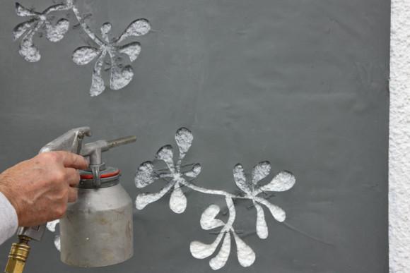 Ansprühen einer Fassaden mit einer Blumen Schablone