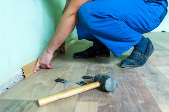 Der CMS Fassadengestaltung GmbH Mitarbeiter prüft die Abstandsfuge vom Laminat zur Wand
