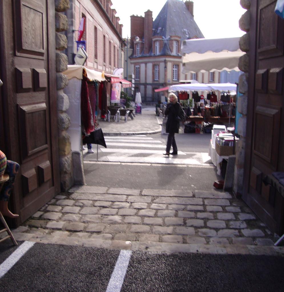Cheminement d'entrée parking et du marché avec au sol obstacle à la roue, la canne et le pied