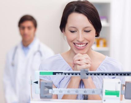 Eine Frau freut sich beim Blick auf die Waage. Eine Hypnosetherapie hat ihr beim Abnehmen geholfen.