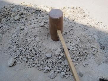原土(山で掘ったままの陶土)を木槌でたたき、粉砕しているところ。フルイに通る大きさに砕く。かなりの重労働