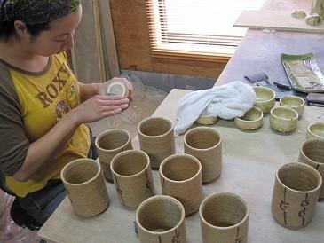 窯から出てきた作品を検品、底磨りしているところ。窯出し直後は土がザラザラしているためヤスリで磨って滑らかにする。