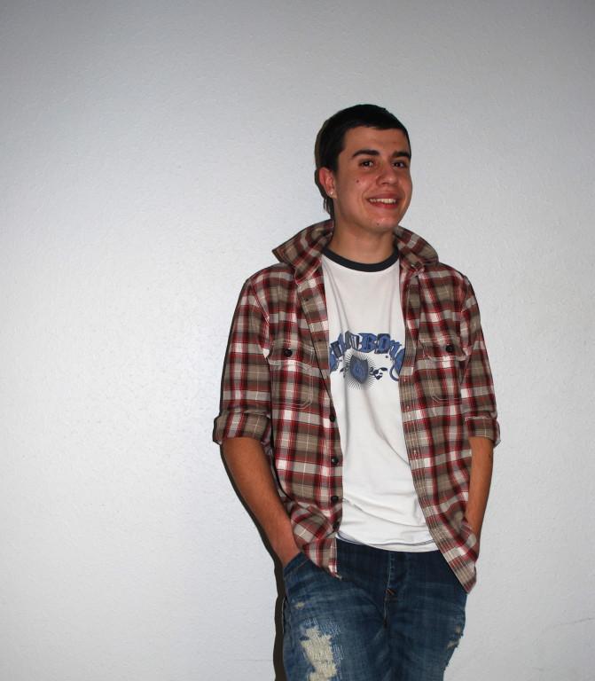 Dylan a mélangé pull à carreau avec un T-Shirt à logo. Ses pantalons sont déchirés ce qui est très à la mode cette année.