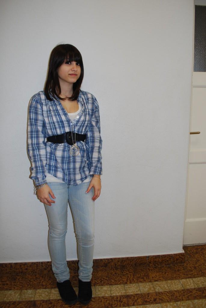 Angela porte un pantalon clair très simple pour ne pas en faire trop, car elle a déjà une chemise à carreaux compliquée. La ceinture lui fait un buste très fin.