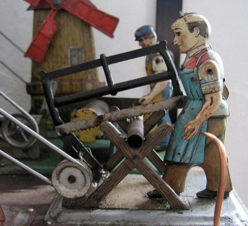 den Arbeiter mit der Gestellsäge/mit der Schrotsäge (hinten)