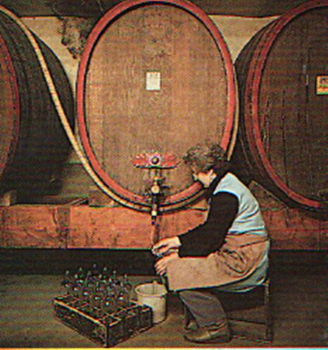 Mitarbeiterin füllt Schnaps aus Holzfass per Hand in Flaschen ab