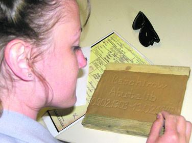 Eine Jugendliche beim gravieren des Namens und der Lebensdaten in einen Namensziegel. Foto: D. Engels, 2.8.2011