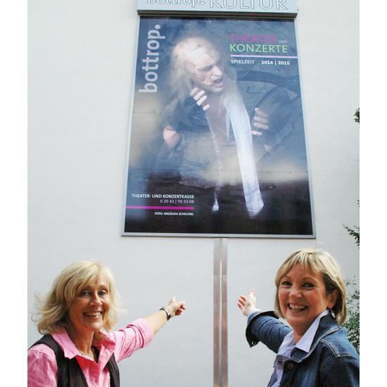 Angelika Schilling (links) und Ilse Orthmann zeigen auf das Plakat am Kulturzentrum.