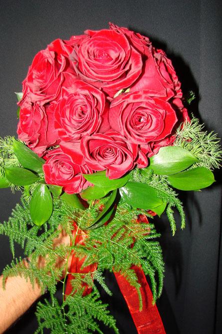 Ramo de novia hecho con rosas rojas .
