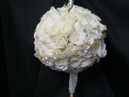 Ramo de novia en forma de bola hecho con rosas blancas.