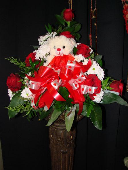 Centro de rosas rojas con peluche.
