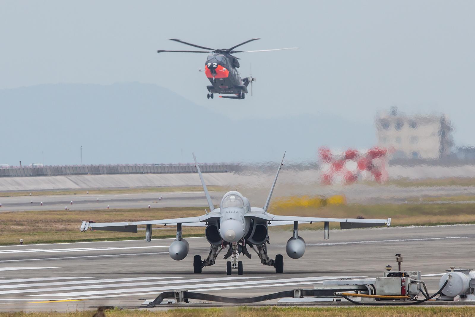 F/A-18A Hornet im Vordergrund, dahinter dreht der Merlin seine Runden.