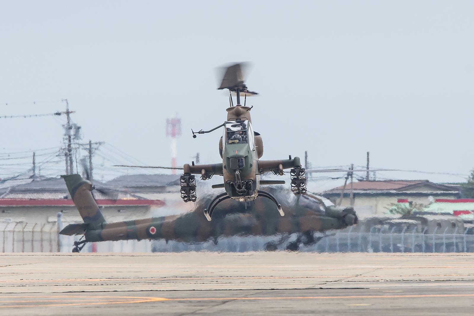 """Eine AH-1S Cobra schwebt auf ihre Abstellposition, im Hintergrund ein AH-64DJP """"Apache""""."""