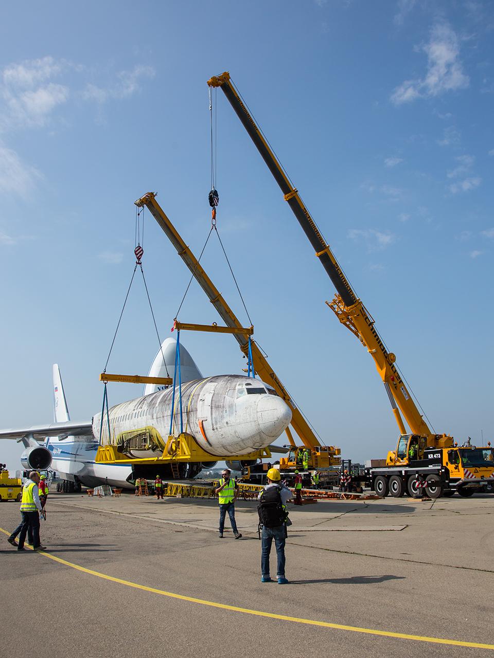 Während der Rumpf der Maschinemit zwei Kränen für den Abtransport fertig gemacht wurde,......