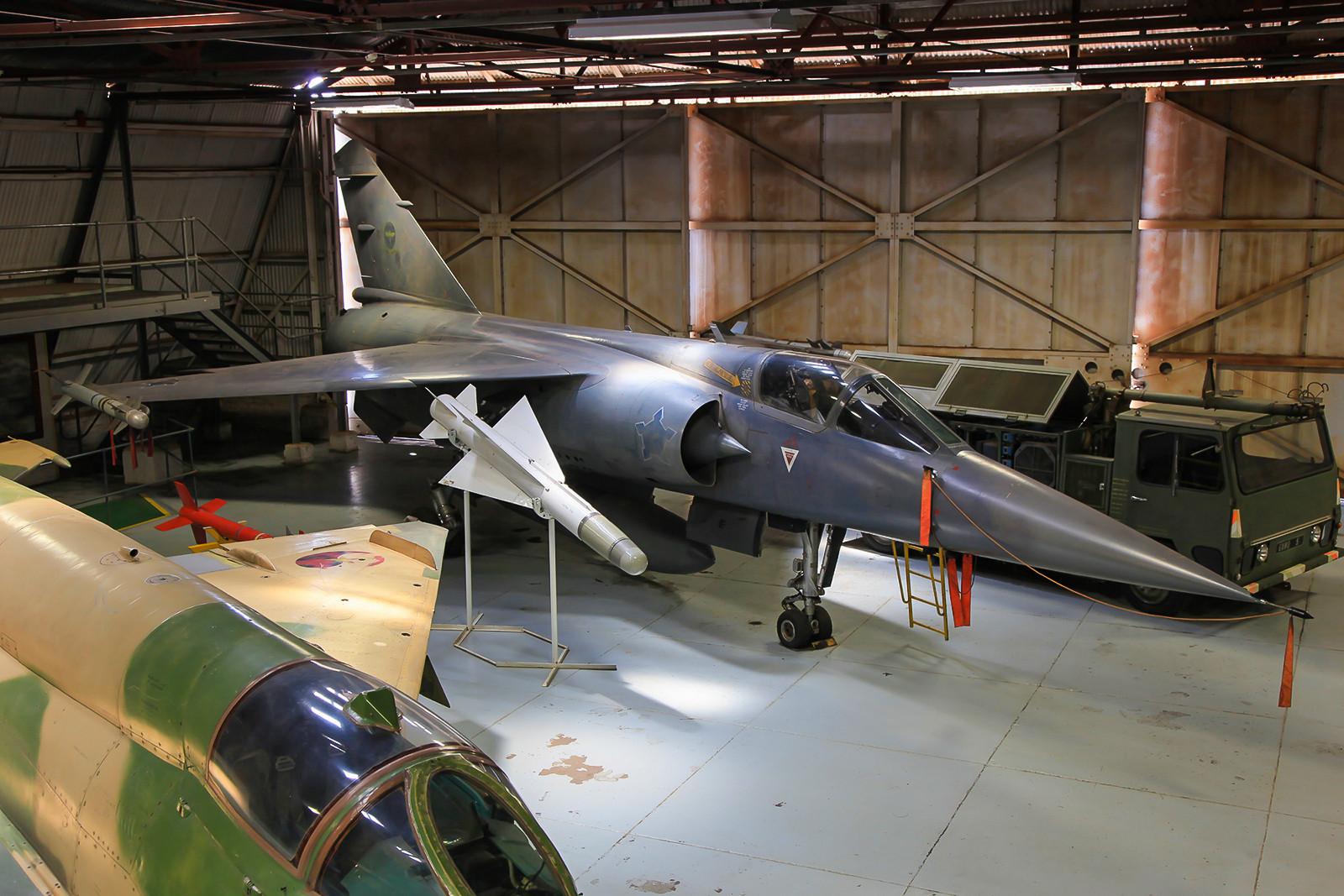 """Etwas dicht zugeparkt, steht die F-1CZ mit der Nummer """"203"""" in einem dunklen Hangar."""