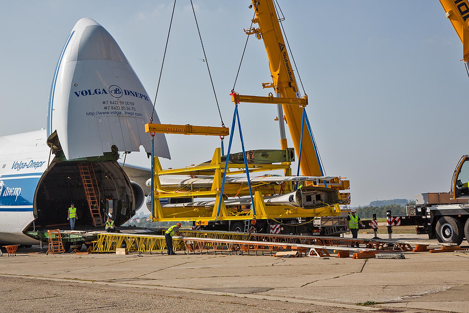 Das Gestell mit den Tragflächen und dem Seitenleitwerk wird aus der Antonov entladen.