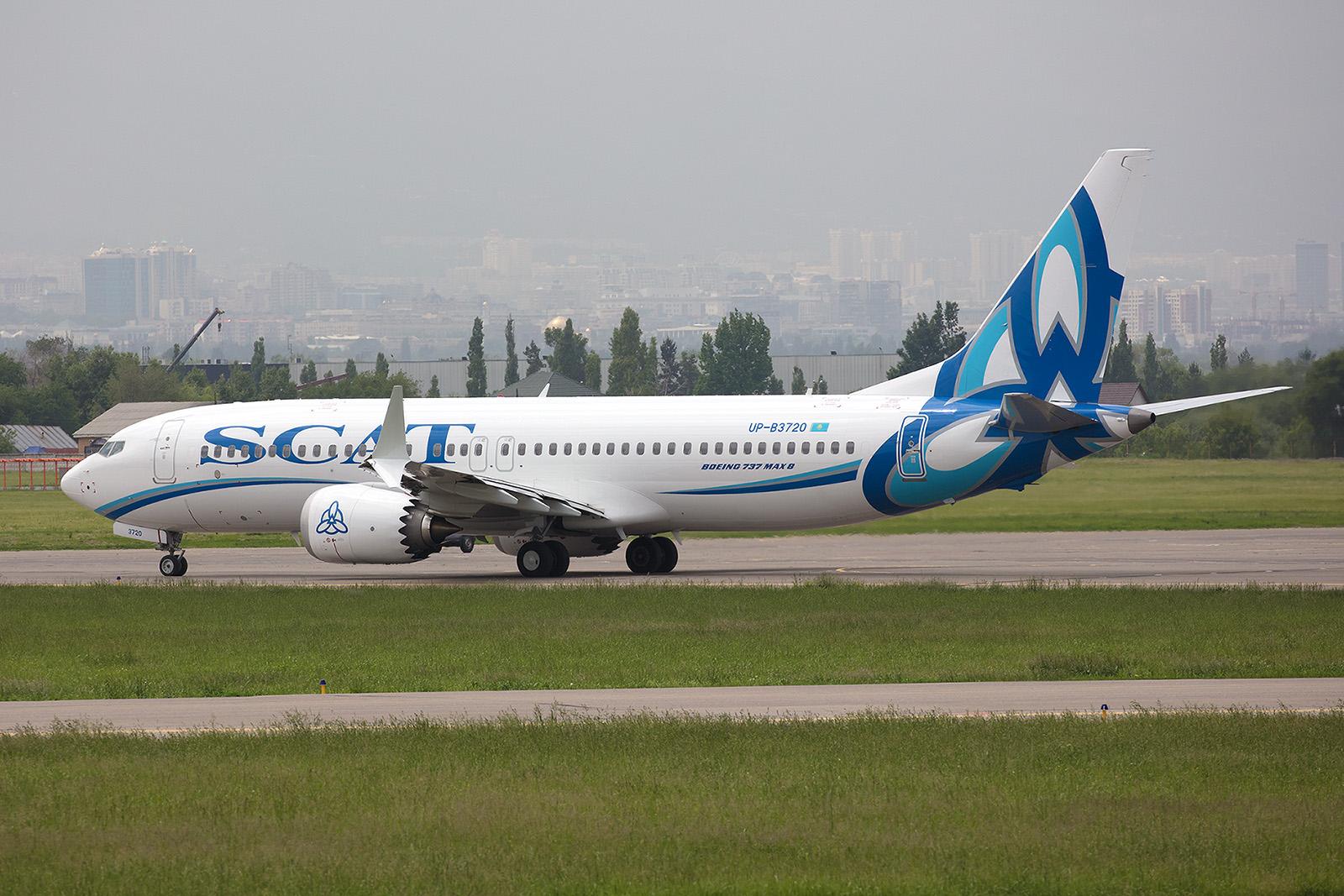 Boeing 7327 MAX 8 der Scat Air auf dem Weg zur Bahn, im Hintergrund die City.