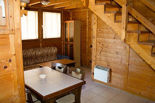 Sala de estar del bungalow con sofá cama y mesas