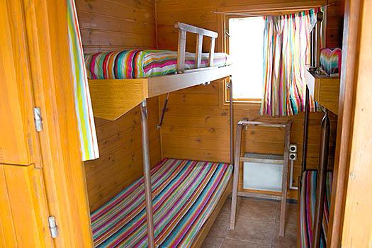 Interior con dos literas y sábanas a rayas