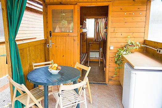 Vista de cerca cabaña de madera y sillas verdes