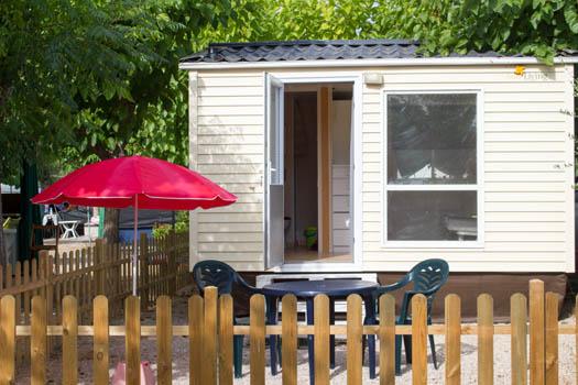 vista exterior de la Mobile-home con la terraza y sombrilla roja