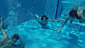 Personas buceando dentro de la piscina