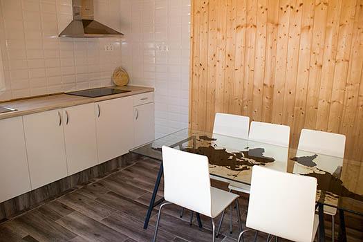 Imagen de la mesa del comedor con cuatro sillas blancas y mesa de cristal