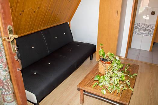 Interor con 2 camas de color negras y mesa de centro en madera