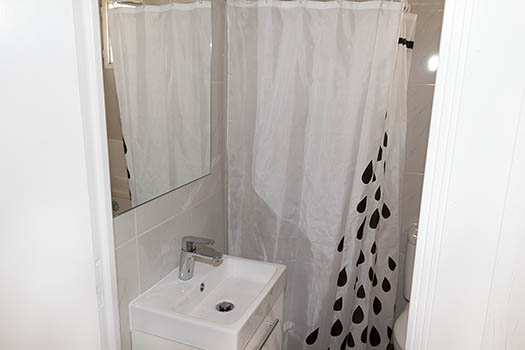 Lavabo de color blanco con cortina a topos negros