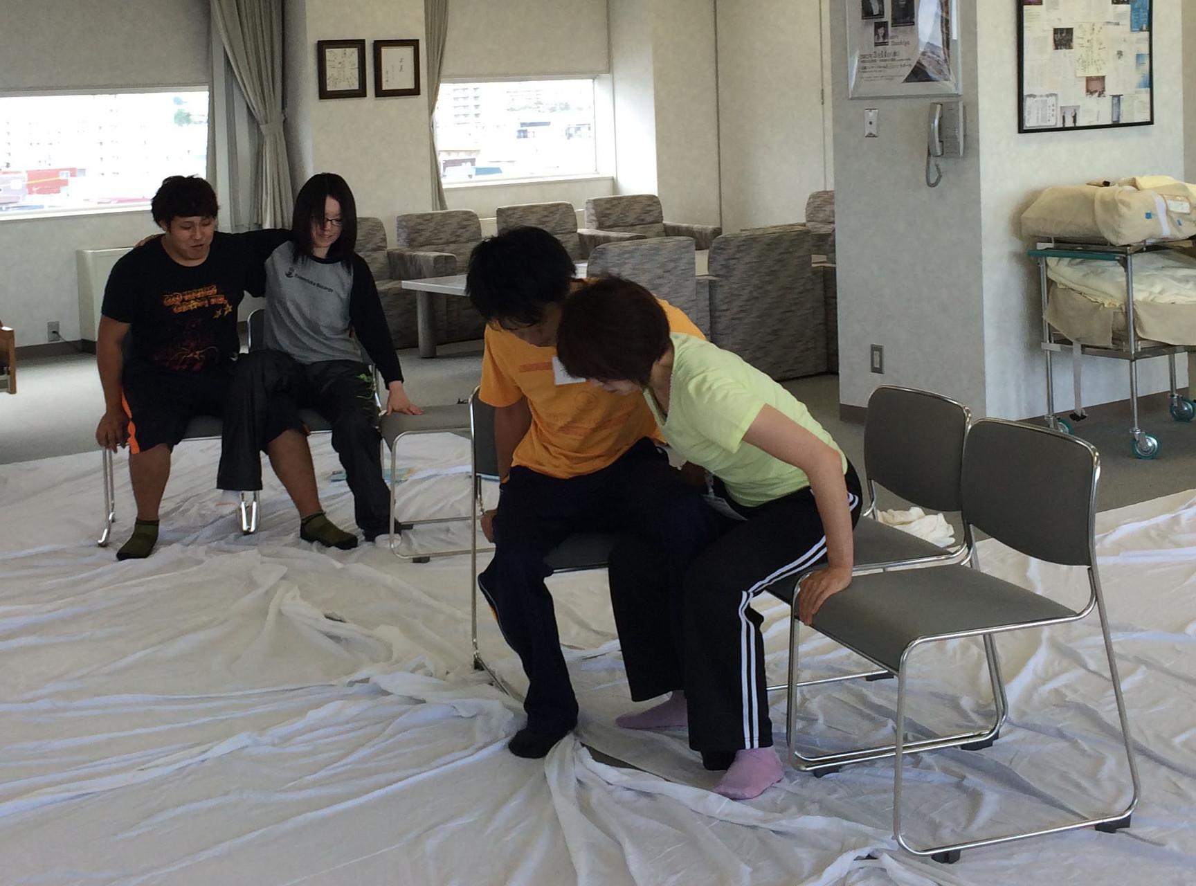 片足に障害がある方の椅子の上での移動を介助しています手前が介助する人