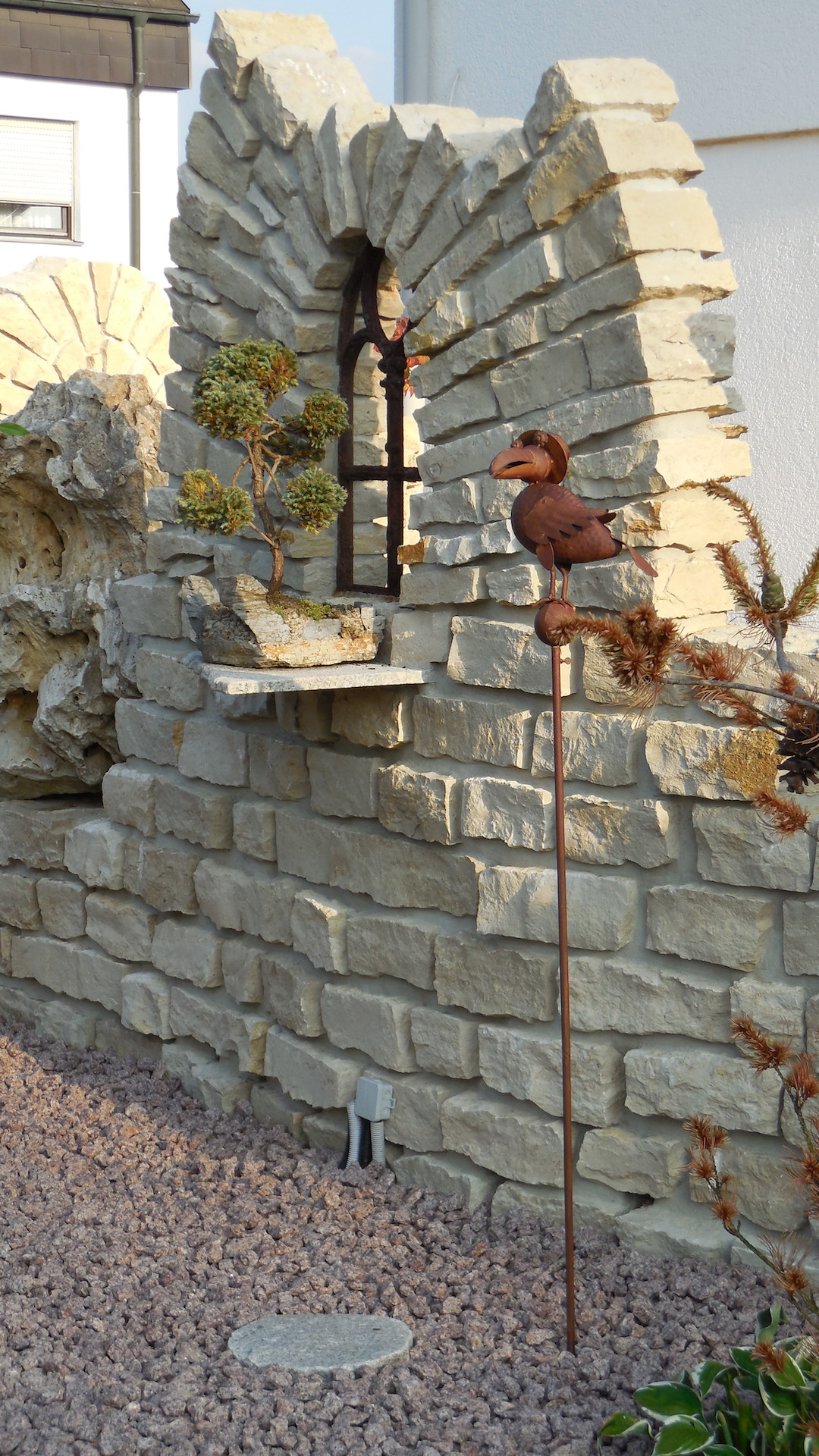 Gusseisernes Fenster und Naturstein - Gartenskulpturen aus Metall