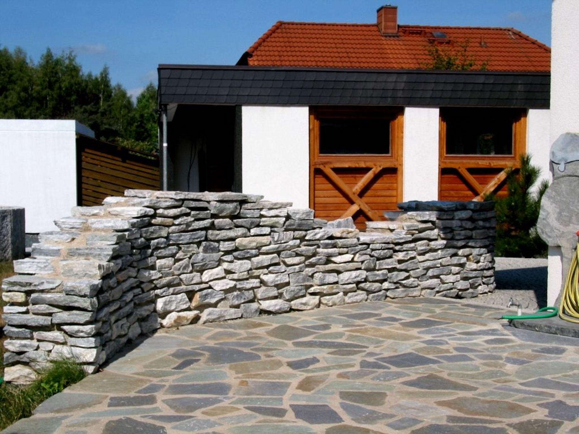 Natursteinterrasse mit Natursteinmauer
