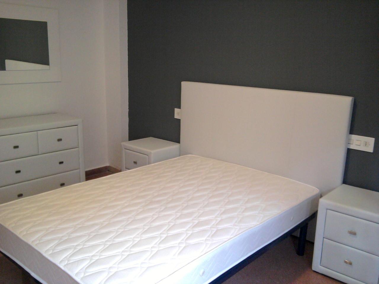 Dormitorio de matrimonio todo en piel blanca .