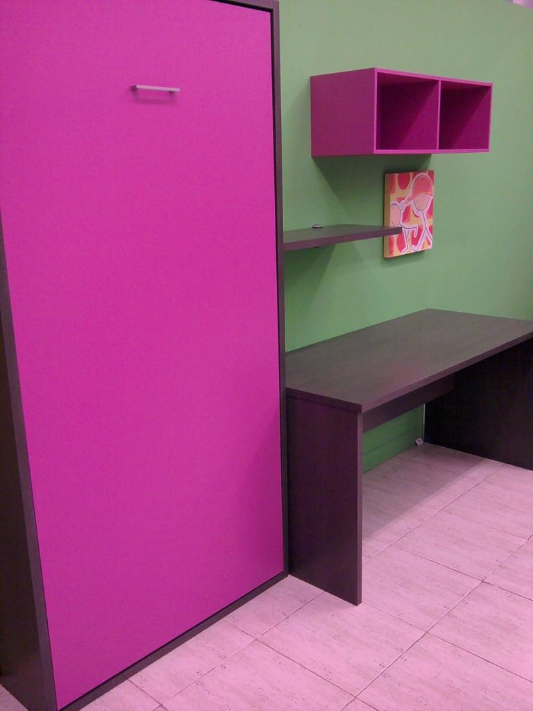 Cama abatible vertical con mesa de estudio y estanterias .