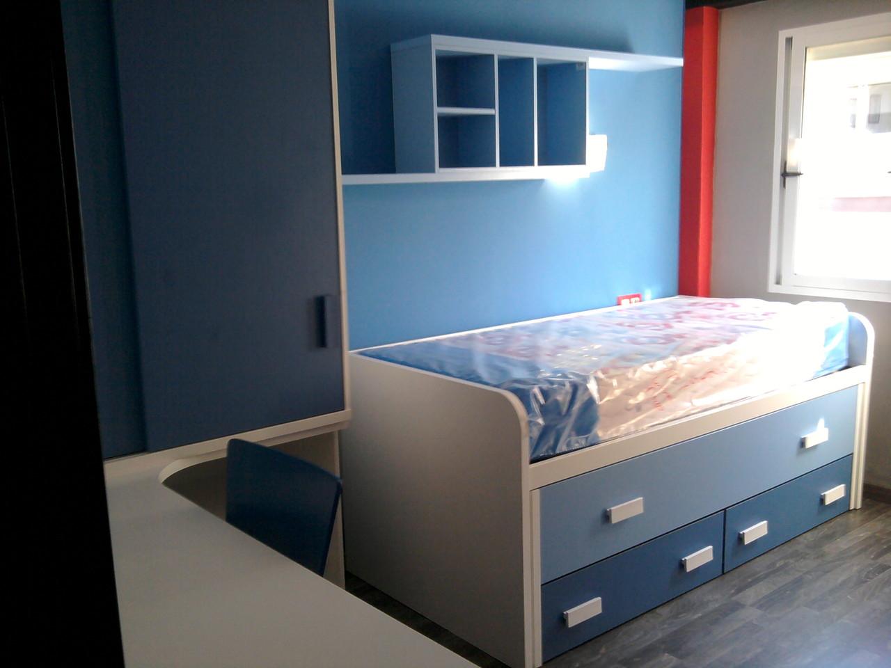 Juvenil completo formado con cama doble mesa de estudio ,armario de puertas correderas y estantería de pared todo ello en azul y blanco .