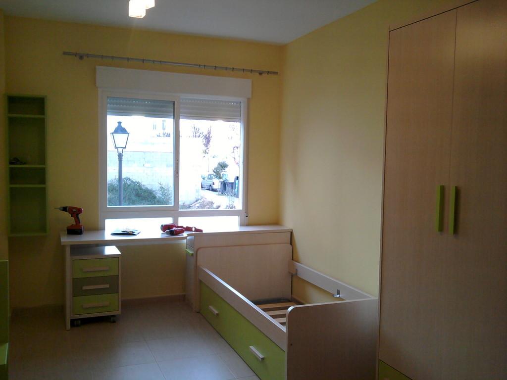 Juvenil sencillo dos camas con armario y mesa de estudio .