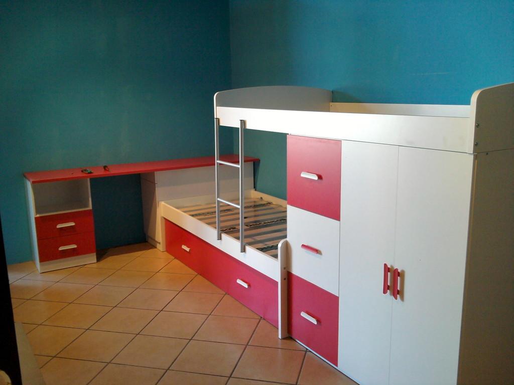 Cama en tren formada por armario cajones contenedores y tres camas dos abajo y una encima del modulo de armario.