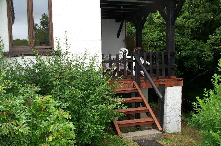 Une terrasse et des pelouses surplombant la vallée avec des meubles de jardin et un barbecue