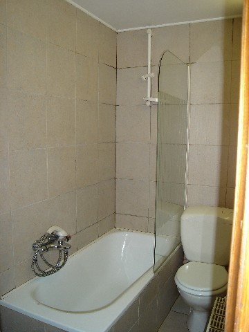 A bathroom with bath - shower, washbasin, WC