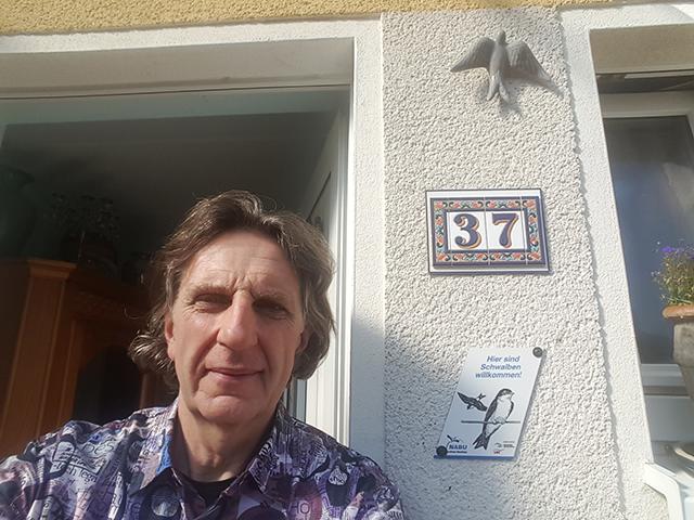 """Herr Teske als stolzer Besitzer der Plakette """"Schwalbenfreundliches Haus"""" / Foto: Teske"""