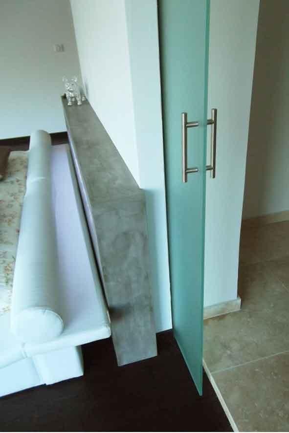 Paroi de verre en galandage dans la partie centrale du mur pour fermeture de la chambre