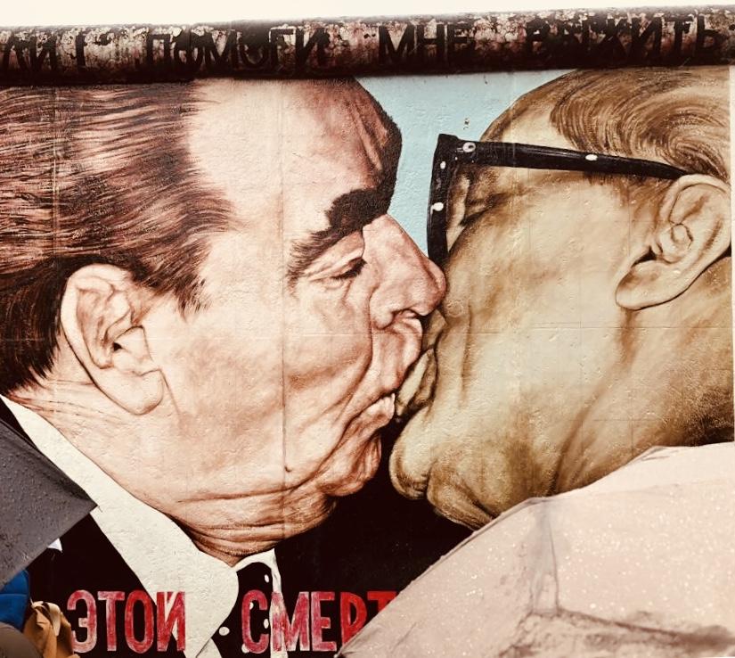 """O mural mais famoso: ¨O Beijo¨ entre o líder soviético Leonid Brezhnev e Erich Honecker, o presidente da DDR. A legenda abaixo: """"Meu Deus, ajuda-me a sobreviver esse amor mortal""""."""