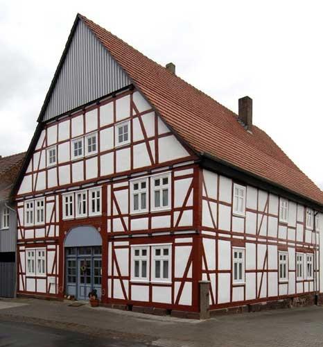 Altes Bauerhaus im Fachwerstil mit braunem Fachwerkständern und weißen Putzfeldern. Zu sehen ist die Giebelseite und eine Dachseite.