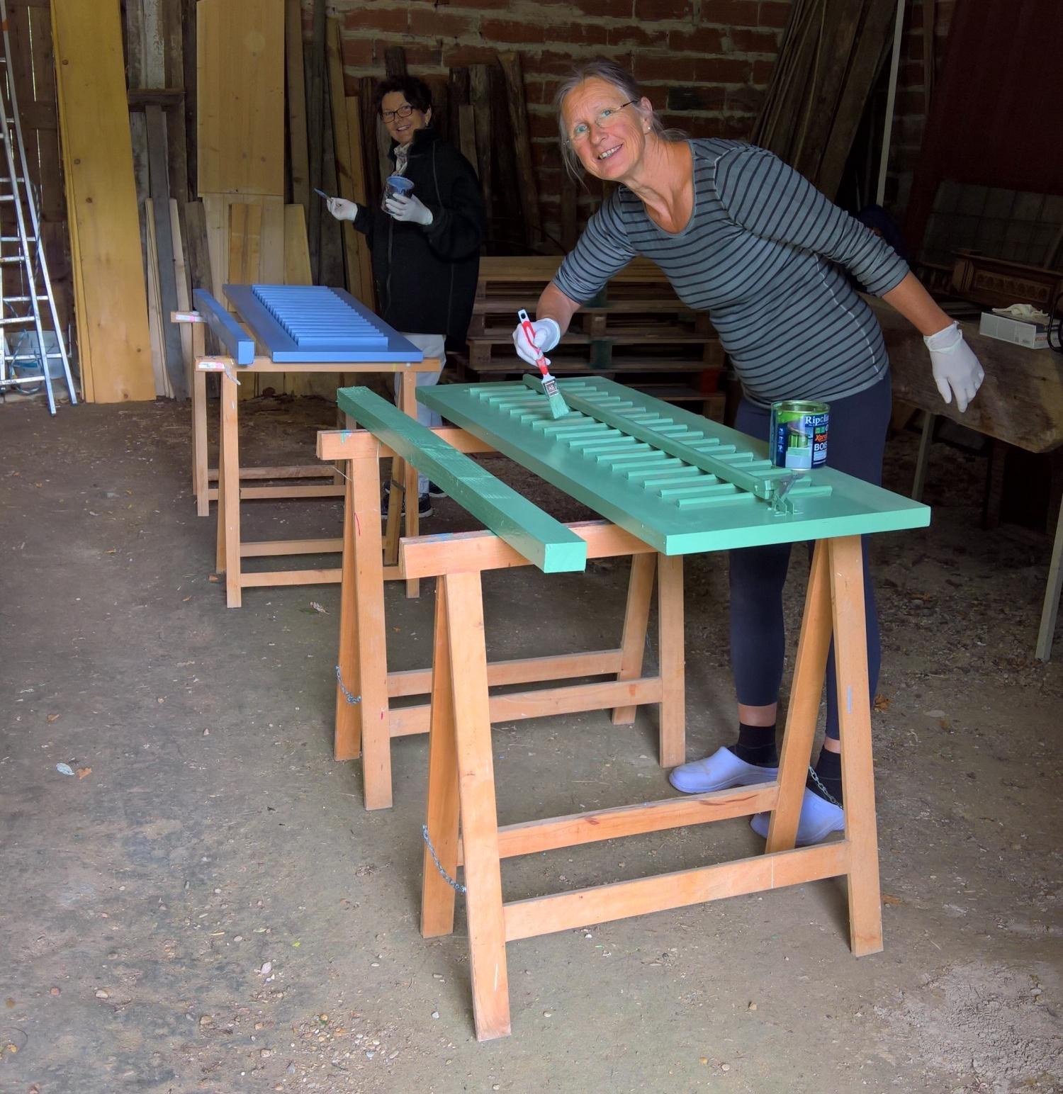 Annette und Isabella, eine Teilzeithelferin, streichen die Läden für die Aussendusche