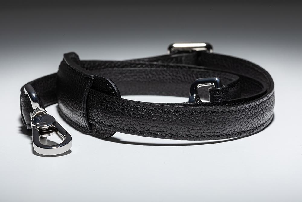 Abnehm- und verstellbarer Leder-Schultergurt (bis ca. 133 cm) mit Schulterauflage und Karabinerverschlüssen